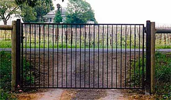 DiFranco Gate & Fence Company - Custom Ornamental Iron Driveway Gates - Western Design Driveway Gate on a Wood Fence - Healdsburg, CA